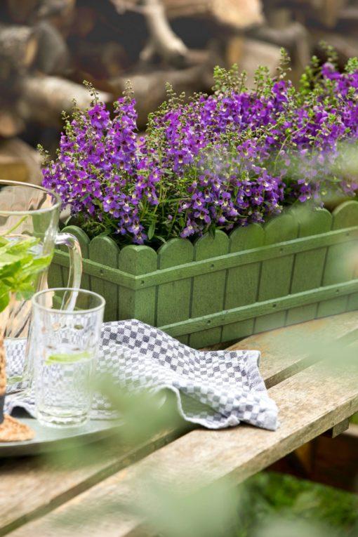 Zielona skrzynka na kwiaty w stylu wiejskiej rezydencji